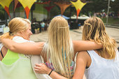 Rear view of three young female friends at music festival